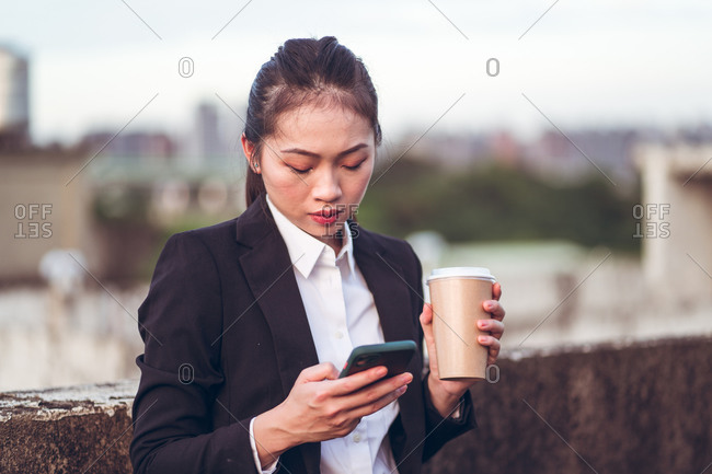 Concentrated young Asian businesswoman in formal outfit holding disposable cup of coffee and messaging on smartphone while standing on rooftop of city building