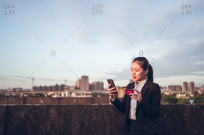 Side view of serious young Asian businesswoman in formal wear holding credit card and smartphone with bank customer service while standing on rooftop of city building