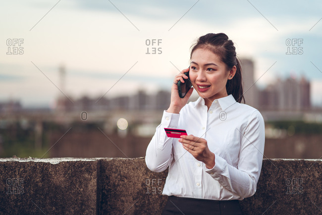 Serious young Asian businesswoman in formal wear holding credit card and having phone conversation with bank customer service while standing on rooftop of city building
