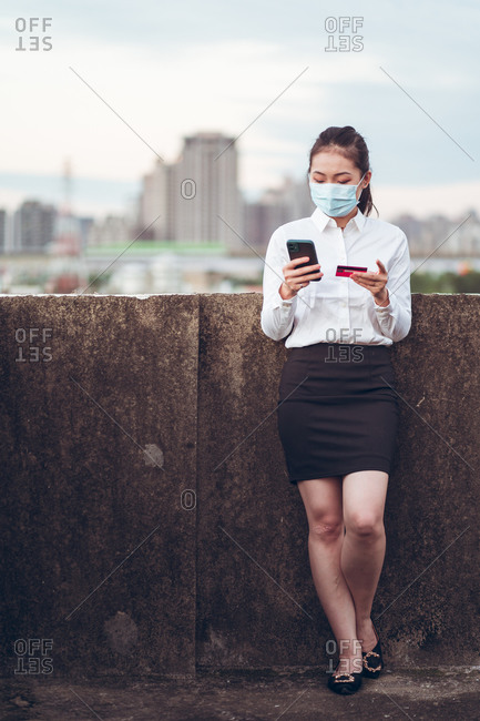 Young Asian female remote employee in formal clothes and medical mask holding credit card and using mobile phone during online payment while standing on rooftop of modern city building