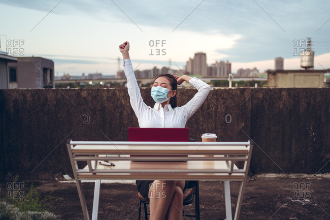 Young Asian female employee in formal wear and protective mask sitting at table with laptop and cup of coffee on rooftop terrace and relaxing after remote work during coronavirus pandemic