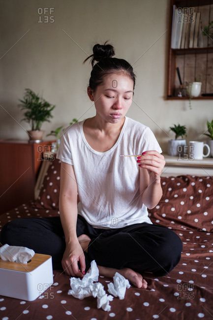 Ethnic female having high temperature and suffering from cold while sitting on bed at home