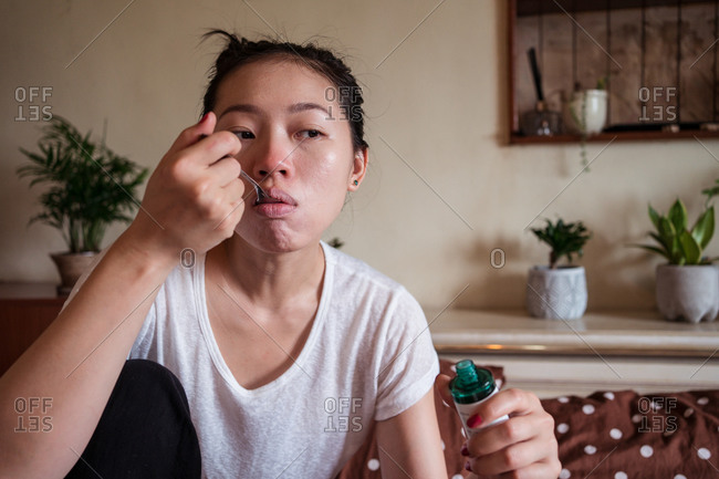 Sick Asian female sitting on bed in apartment and taking cough syrup while having flu