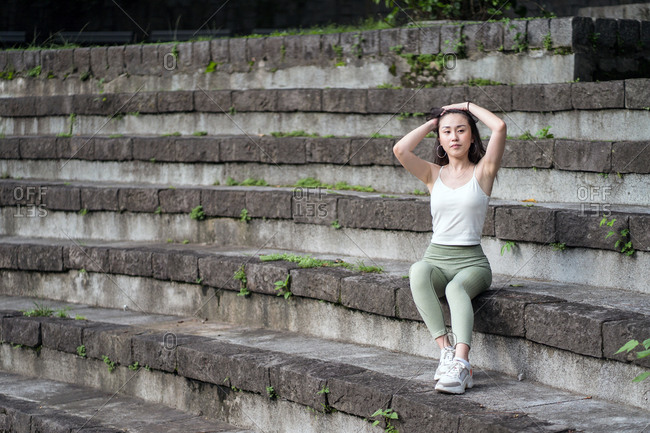 Full length sporty Asian lady wearing tight casual clothes resting on old stone staircase in park