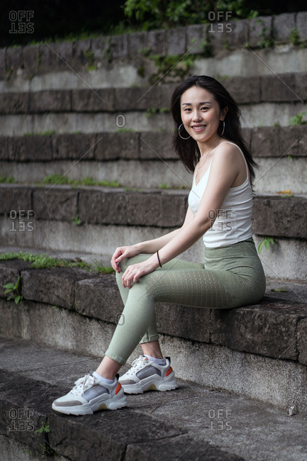 Side view full length sporty Asian lady wearing tight casual clothes resting on old stone staircase in park while looking at camera happily