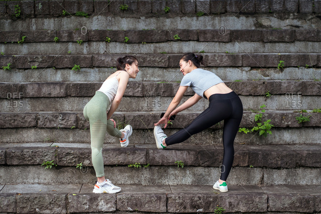 Back view of fit positive Asian girlfriends in sports clothes and sneakers stretching legs on abandoned stairs while looking at each other