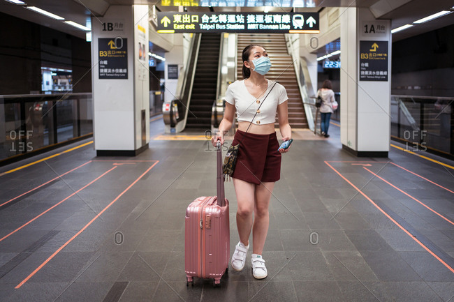 Full length young Asian female in mini skirt walking with suitcase in railway station while waiting for train