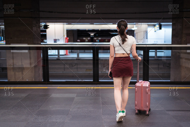 Back view of unrecognizable young female in mini skirt walking with suitcase in railway station while waiting for train