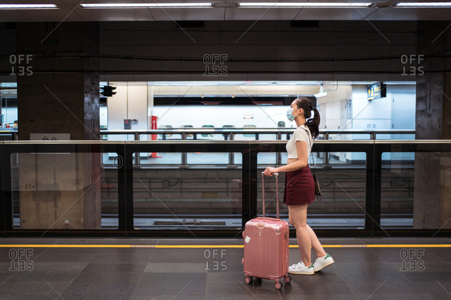 Full length side view young Asian female in mini skirt walking with suitcase in railway station while waiting for train