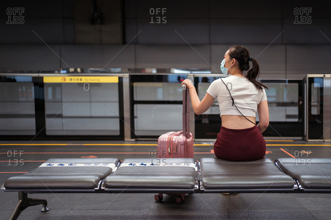 Back view of young concentrated Asian lady wearing mini skirt and face mask sitting on bench with suitcase waiting for the train in the station