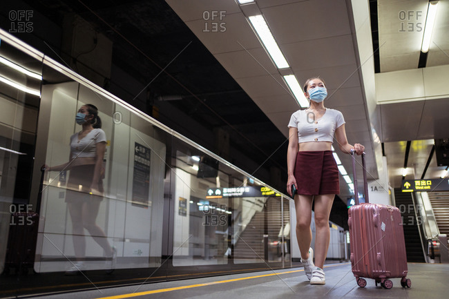 Full length calm young Asian female in casual clothes and face mask with suitcase ready to board modern fast train cabin in contemporary railway station