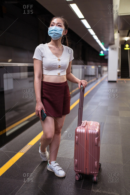 Full length young Asian female in mini skirt standing with suitcase in railway station while waiting for train