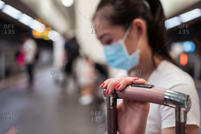 Young concentrated Asian lady wearing mini skirt and face mask sitting on bench with suitcase waiting for the train in the station