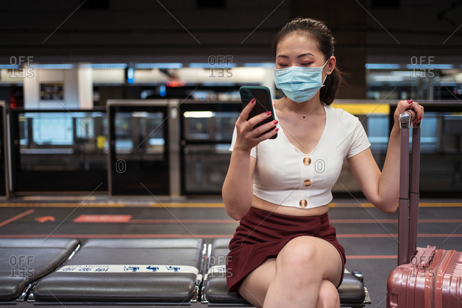 Young concentrated Asian lady wearing mini skirt and face mask browsing mobile phone while sitting on bench with suitcase in train station