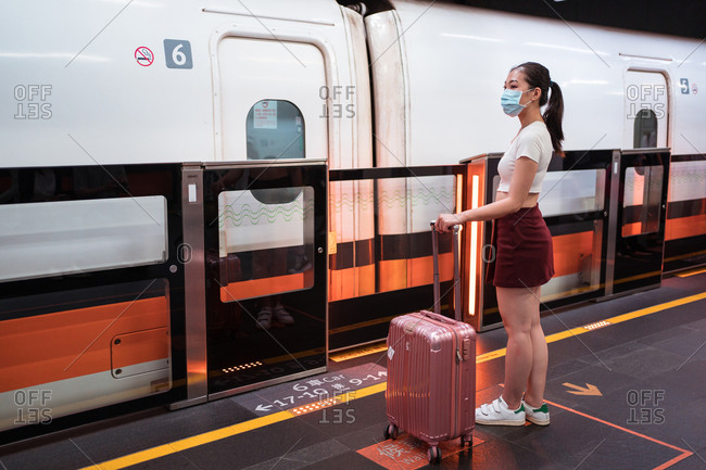 Side view full length calm young Asian female in casual clothes and face mask with suitcase ready to board modern fast train cabin in contemporary railway station