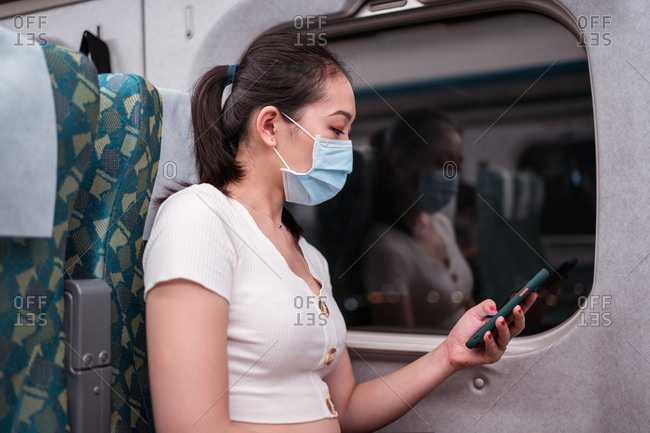 Side view slim young Asain lady traveling by train browsing modern cellphone while sitting on comfortable passenger seat near window and suitcase during coronavirus epidemic