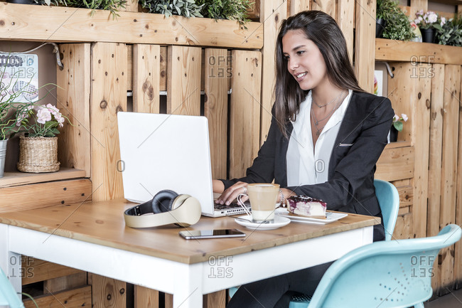 Smiling businesswoman in formal wear working on laptop while sitting in front plate with tasty cheesecake and glass of coffee in cafeteria