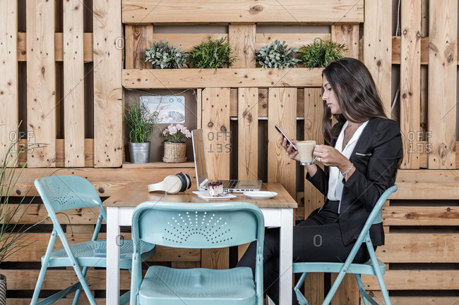 Side view of stylish businesswoman chatting on cellphone while sitting with glass of latte in front of laptop and cheesecake in cafeteria during break