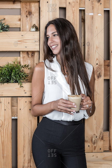 Dreamy lady in formal clothes and manicure standing near wooden fence with glass of hot coffee while looking away in cafeteria