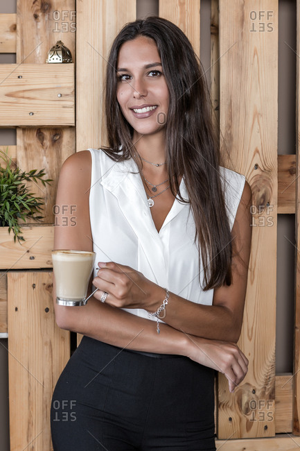 Dreamy lady in formal clothes and manicure standing near wooden fence with glass of hot coffee while looking at camera in cafeteria