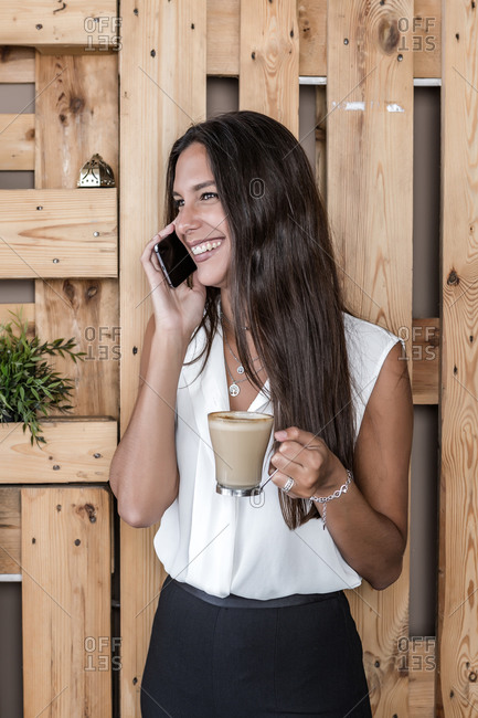 Dreamy lady in formal clothes standing near wooden fence with glass of hot coffee while looking away and speaking on smartphone in cafeteria