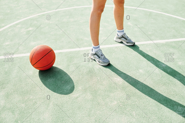 High angle of crop anonymous female basketball player standing near ball on marking line in center of court during training in sunny day