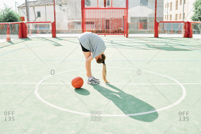 Full body side view of unrecognizable female basketball player performing forward bend exercise while warming up during training on sports ground