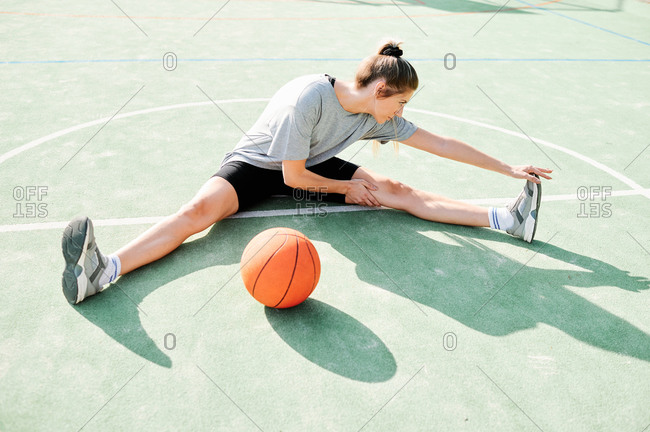 Full body high angle view of young female basketball player sitting on court near ball and doing stretching exercise before game