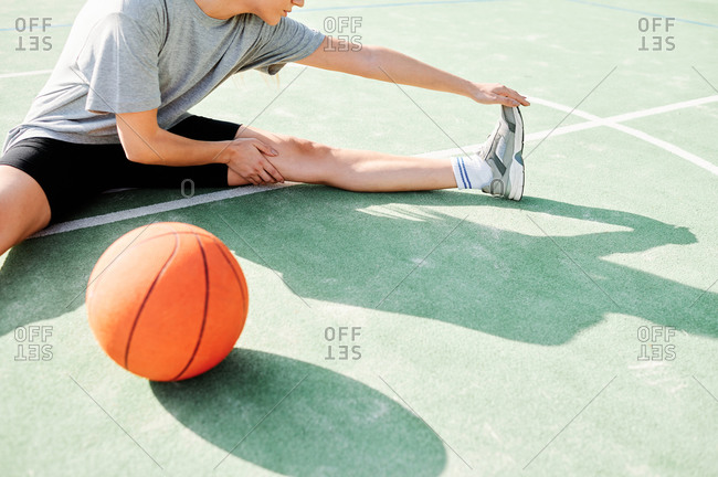 High angle view of young female basketball player sitting on court near ball and doing stretching exercise before game