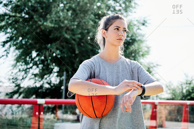 Low angle of serious young female in sportswear holding basketball ball and checking time on wristwatch while waiting for friend for training together on court