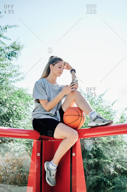 Low angle side view of young female in sportswear with basketball ball sitting on metal railing and browsing mobile phone while resting after training on sports ground in sunny summer day