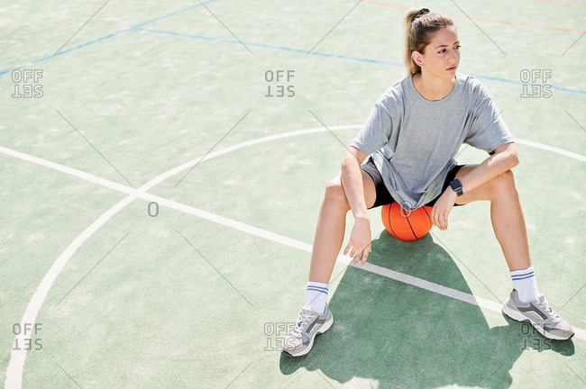 High angle view of young female basketball player sitting on ball on the basketball court