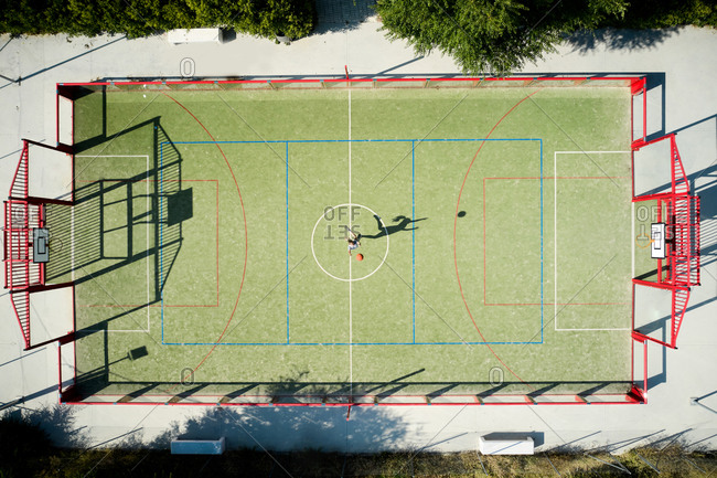 From above drone view of anonymous sportswoman jumping and throwing ball while training on basketball ground in sunny day