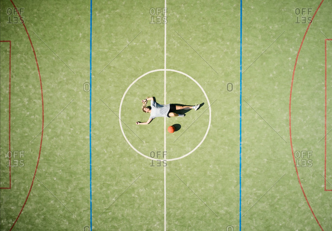 From above drone view of relaxed female basketball player with ball lying on center circle of court while resting after training