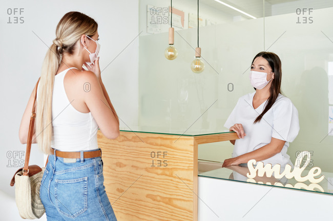 Blond female client in medical mask talking with receptionist while visiting modern dental clinic during pandemic