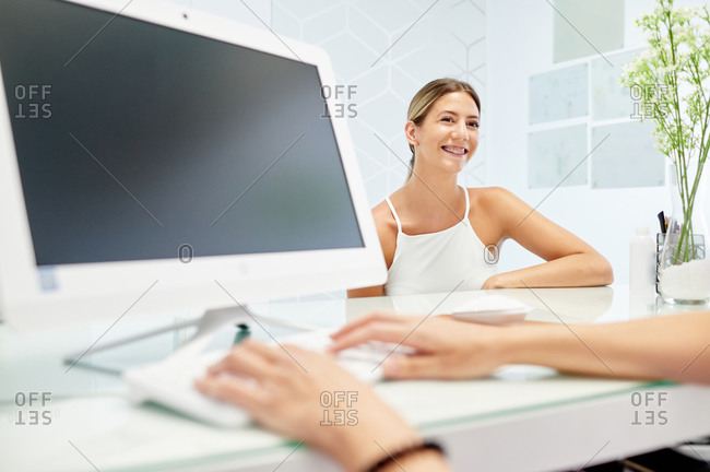 Female patient watching diagnostic results on computer while visiting cropped unrecognizable dentist in modern clinic