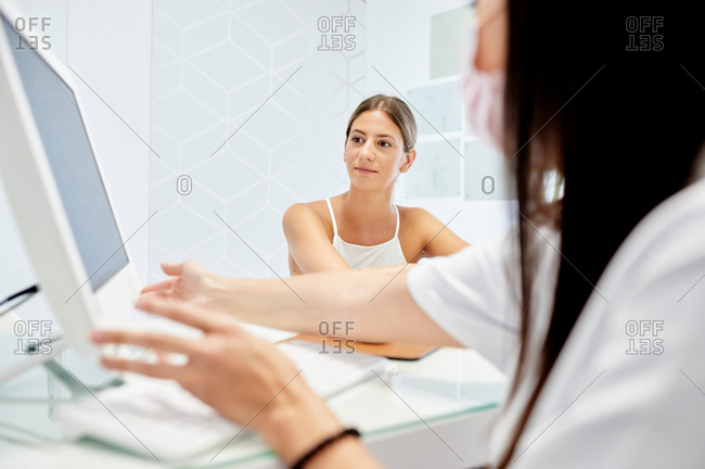 Female patient watching diagnostic results on computer while visiting dentist in modern clinic