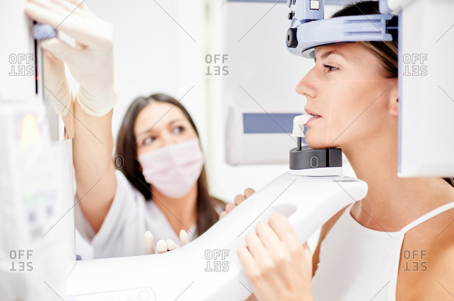 Female dentist using computer while making X ray scan to young woman in contemporary dental clinic