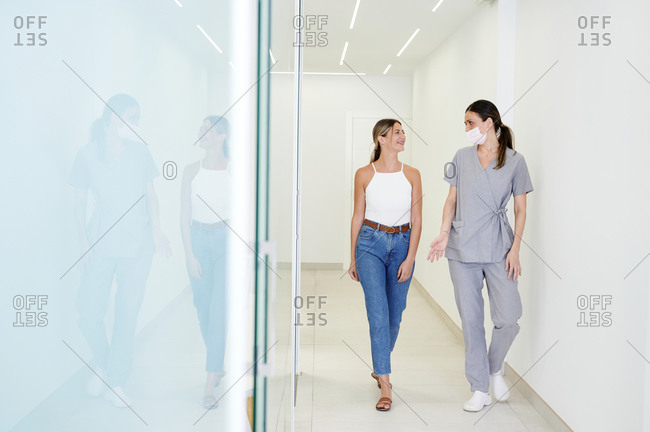 Full body woman visiting professional dental hospital and talking to dentist while walking in light hallway