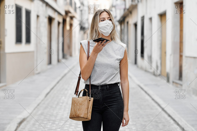 Young female in stylish outfit wearing a face medical mask messaging on mobile phone while walking on the street looking away