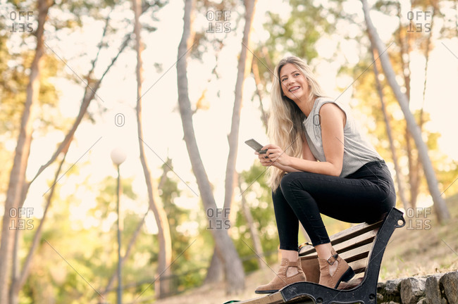 Low angle of cheerful young female in trendy outfit sitting on bench and browsing smartphone while resting in green park in sunny day