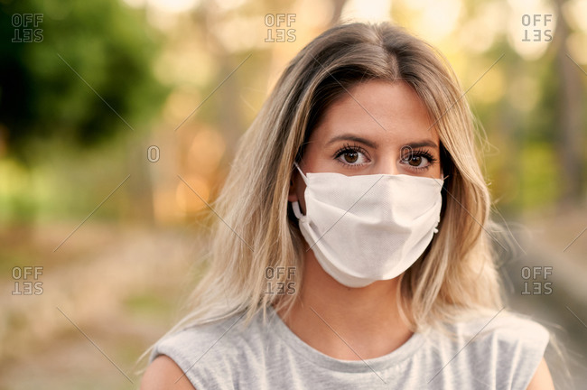 Young female in casual clothes and protective mask for coronavirus prevention looking at camera while standing on alley in green park