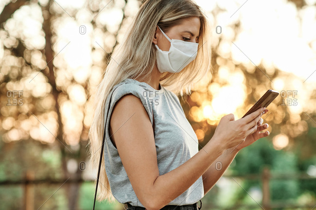 From below cheerful young female in trendy outfit and protective mask for coronavirus prevention browsing on smartphone while standing in green park in sunny day