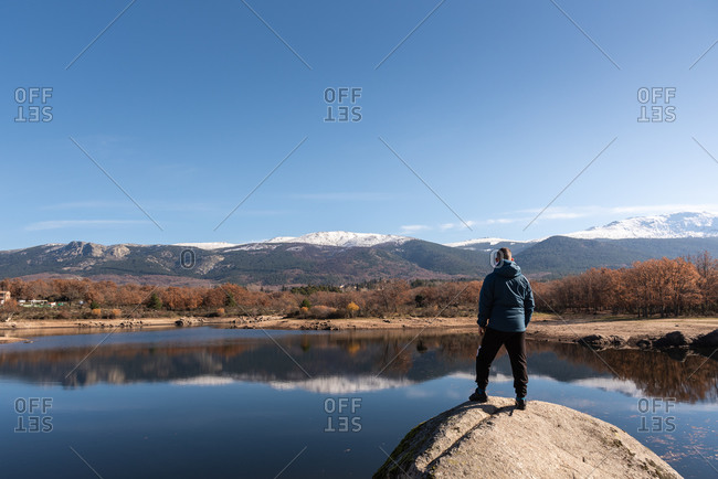 Back view of male explorer in warm clothes standing on rock at lakeside and admiring spectacular mountainous landscape