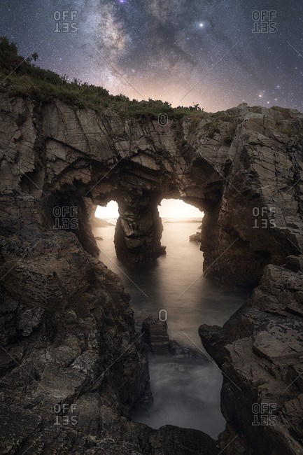 Amazing scenery of sea coast with calm water and rocky cliffs with caves under dark sky with Milky Way