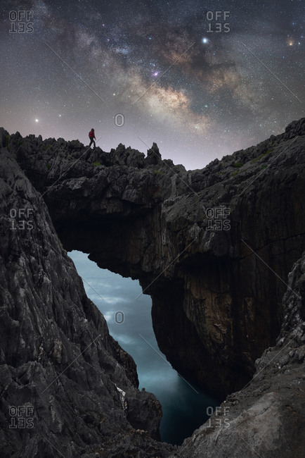 Distant silhouette of anonymous traveler standing on rough rocky mountain with cave near sea and enjoying spectacular scenery with luminous sky and Milky Way