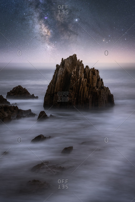 Amazing scenery of sea coast with calm water and rocky cliffs under dark sky with Milky Way