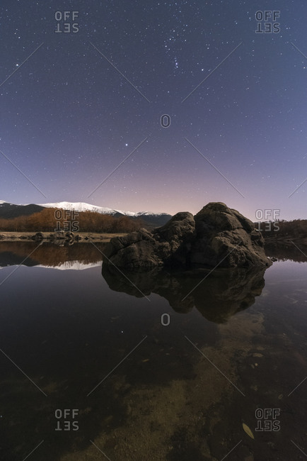 Amazing scenery of lake and snow mountains under dark sky with stars and a rock in first plane