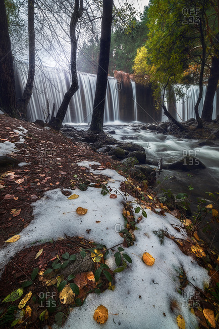 Picturesque scenery of rapid river with wide waterfall and rocky bottom flowing through autumn forest with colorful trees in cloudy day