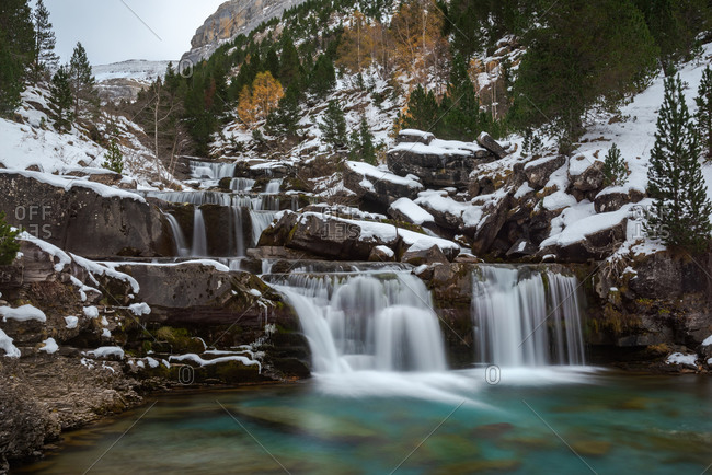 Picturesque landscape of small waterfall and pool with turquoise water located among boulders covered with snow against green coniferous forest and cloudy blue sky in mountainous terrain